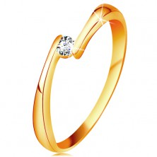 Ring made of yellow 14K gold - clear diamond between the narrowed ends of shoulders