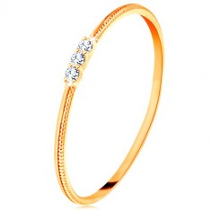 Ring made of yellow 9K gold - narrow shoulders with notches, three clear zircons