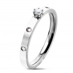 A steel ring in silver colour – a round zircon in claw setting, clear zircons, 3 mm
